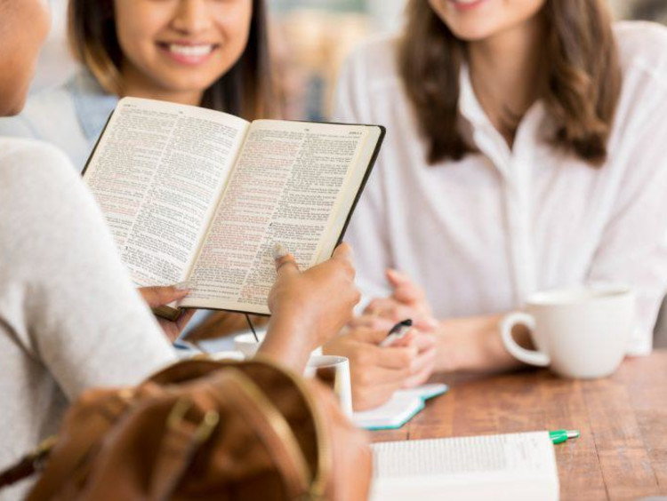 one person reading the bible with two people in the background