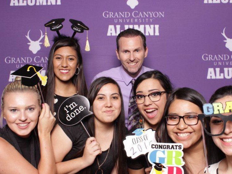 Jim Mostofo poses with recent Education graduates in GCU alumni photo booth