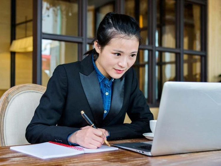 girl writing and looking at a computer