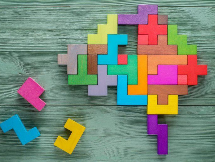 Colored puzzle pieces form a brain shape with a few missing pieces