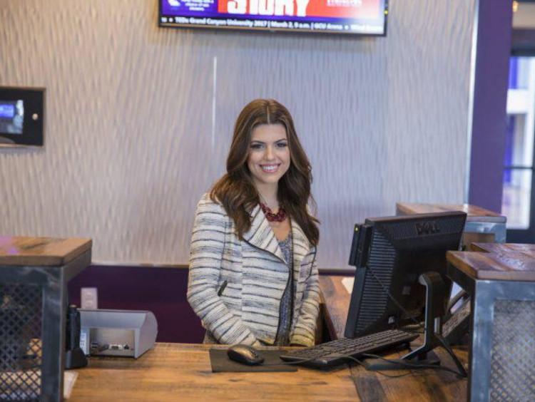 Front desk clerk of the GCU Hotel smiles