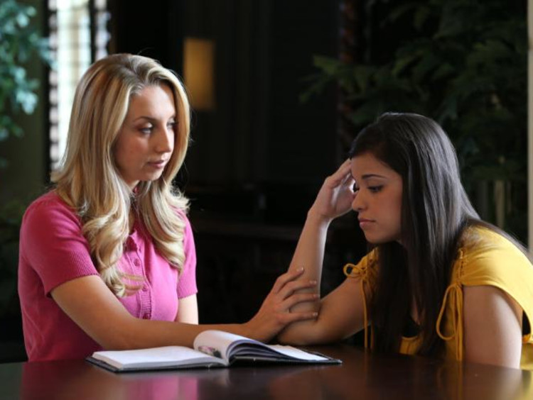 Blonde female high school counselor consoles female brunette student