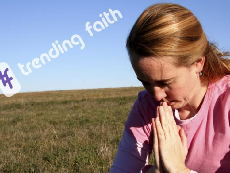 A woman praying in a field under the Trending Faith logo