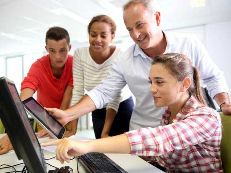 girl pointing to a computer and three other people watching