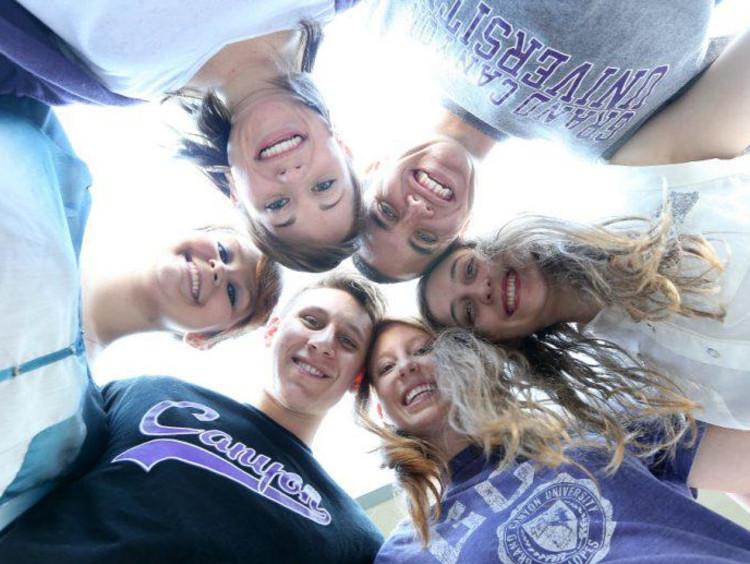 A group of GCU students huddling together
