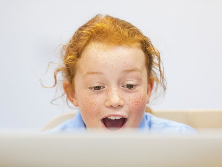 Red-headed girl looks at laptop