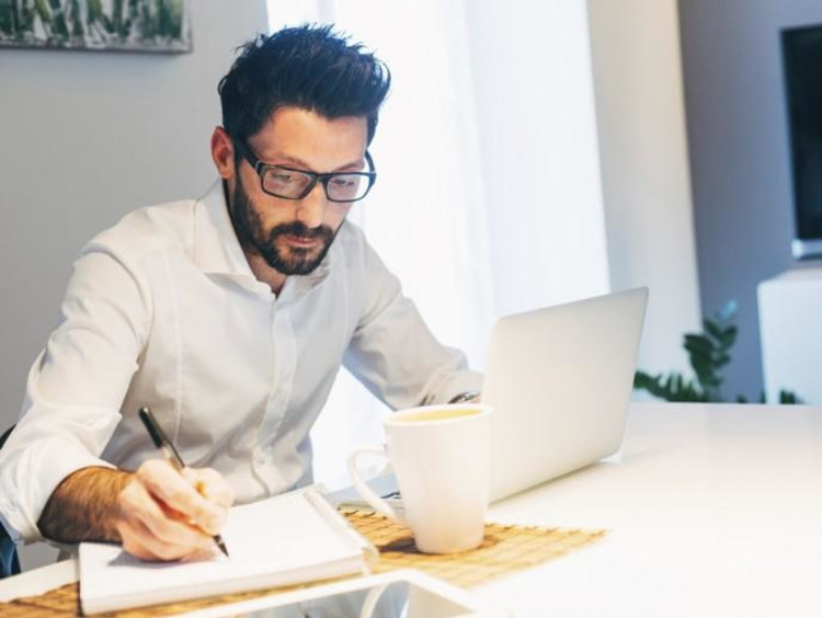 man writing on notebook with laptop in front of him
