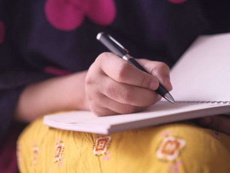 A student taking notes on a paper pad