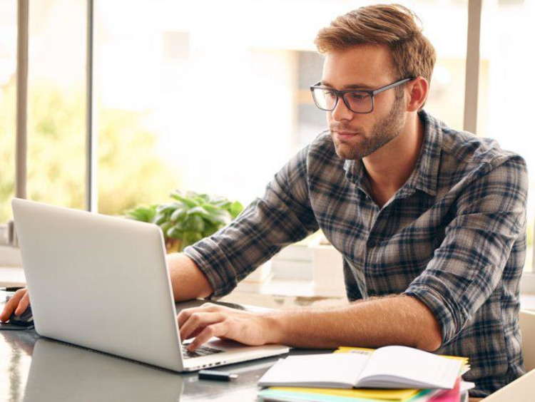 Man in plaid shirt researches online degree programs on laptop