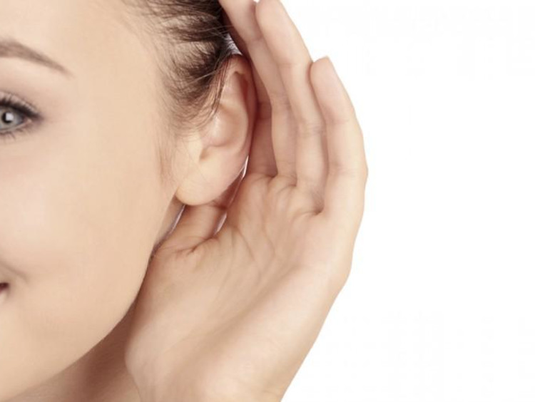 a girl cupping her ear