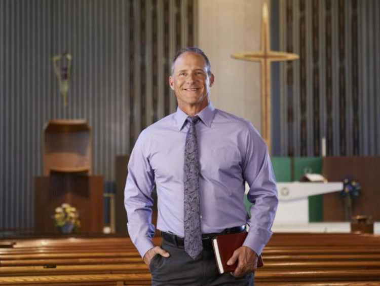 A man in a purple shirt standing in a church