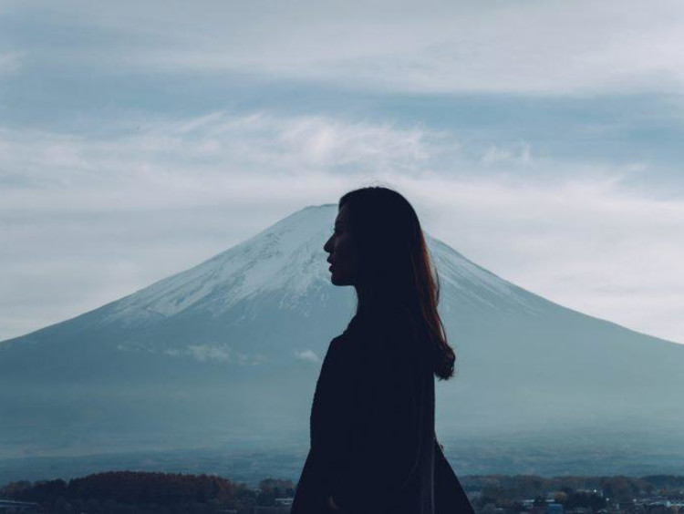 A girl looking out into the distance with a mountain behind her