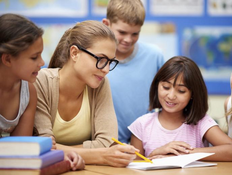 Teacher points to a word in book with students huddled around her