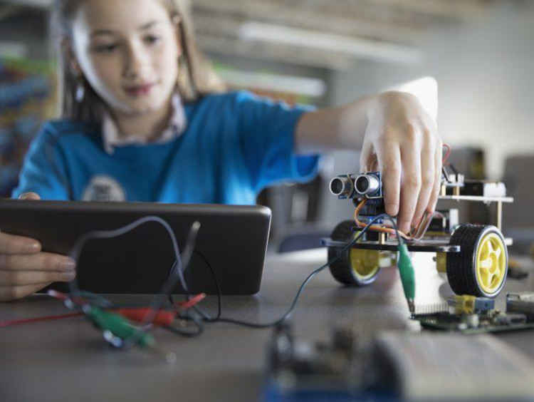 Young girl working on a robot