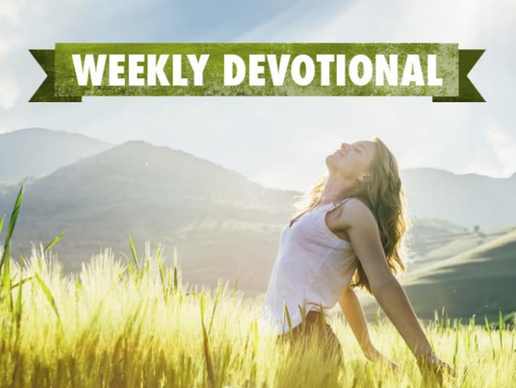 A joyful woman in a field under the Weekly Devotional banner