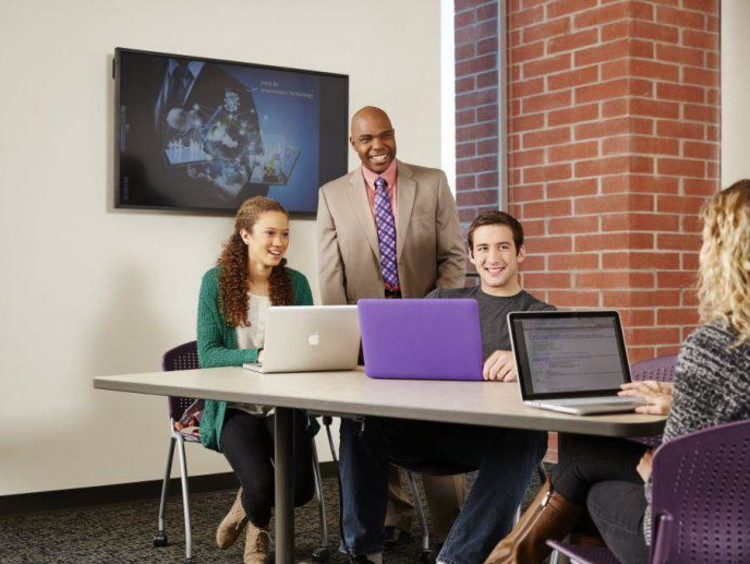 A professor stands behind three students seated and using laptops
