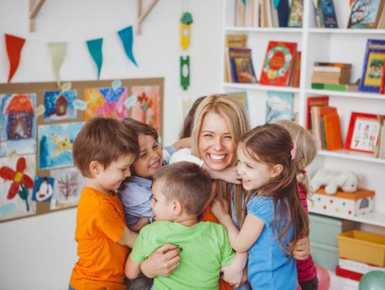 Preschoolers give a teacher a group hug