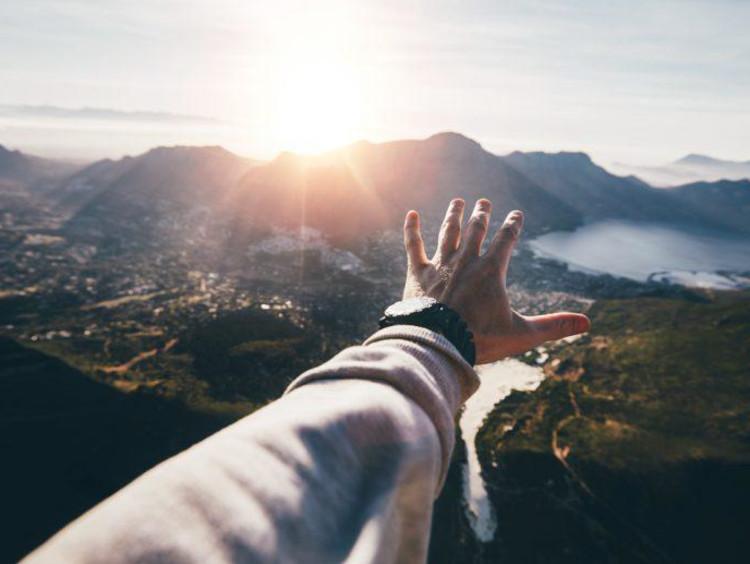 arm reaching towards mountains