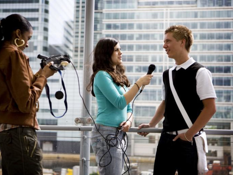 a girl interviewing a guy with camera and mic