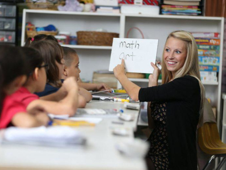 teacher holding whiteboard and teaching students