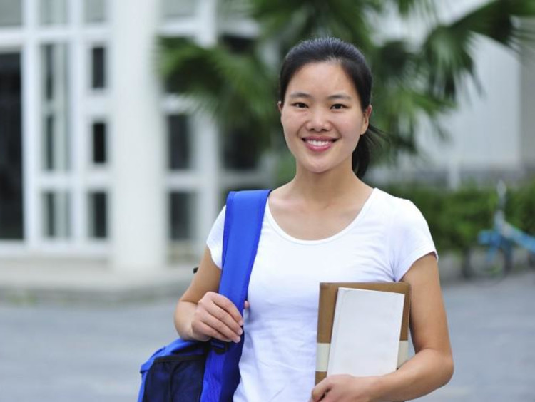 girl holding notebook and wearing backpack smiling