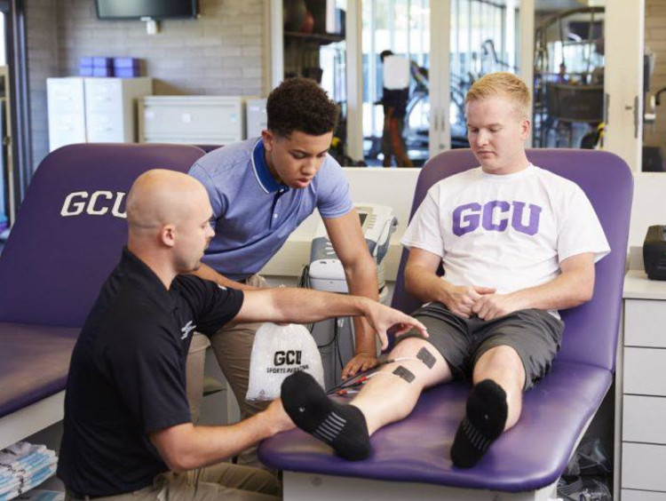 GCU student in the sports medicine room with a technician