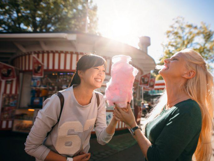 two girls at a carnival eating cotton candy