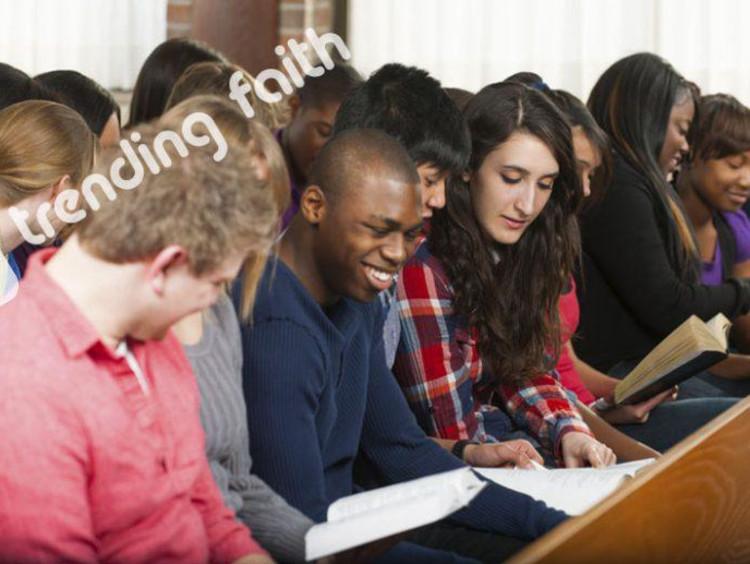 Young Adults gather in church setting gathered over a book