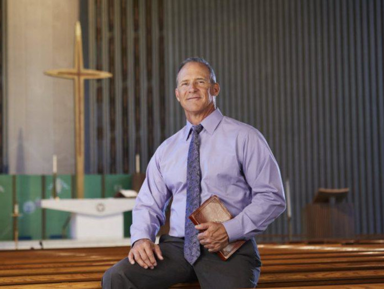 Man in a purple shirt holding a Bible