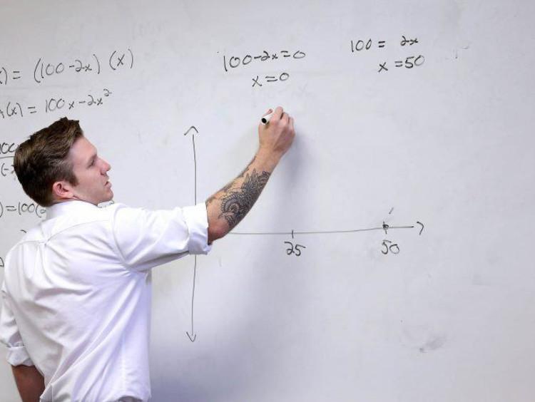 Math teacher writing on the board