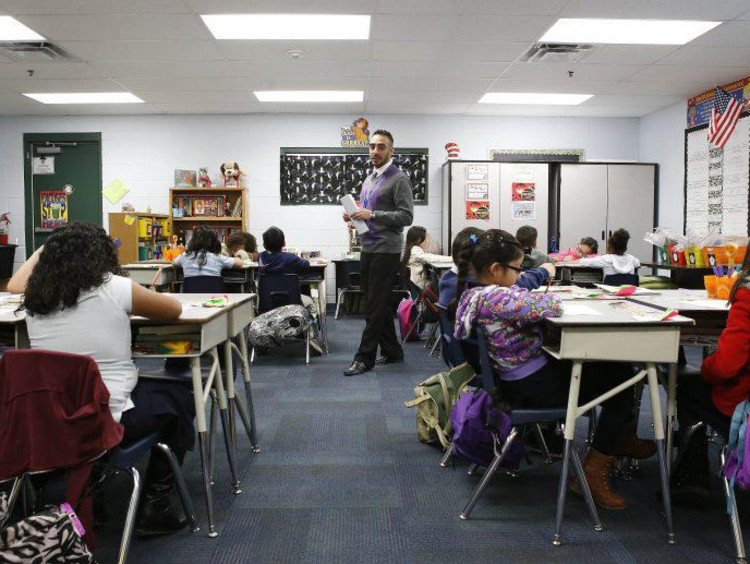 Hispanic male teacher paces classroom while students work