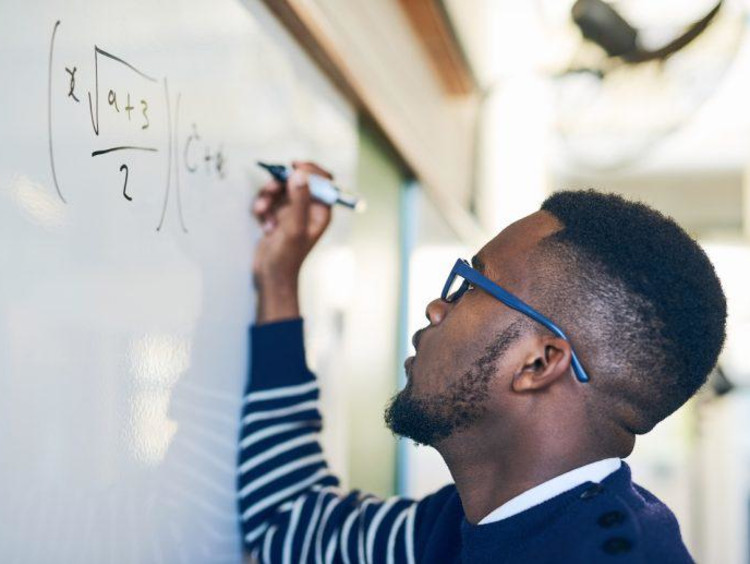 Man writing math on the board