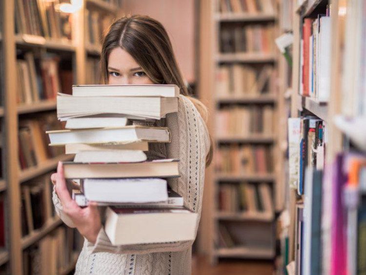 Woman in library with books stacked in arms