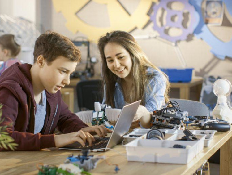 Students look excited on laptop with robotic equipment on table