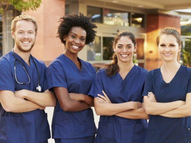 Four nurses standing with arms crossed