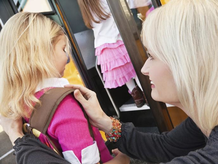 Parent helping girl with backpack