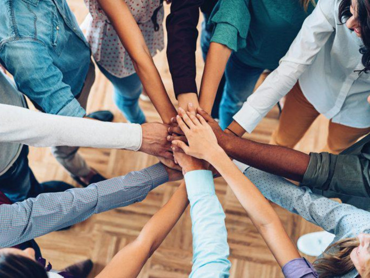 Team members combined hands to promote solidarity