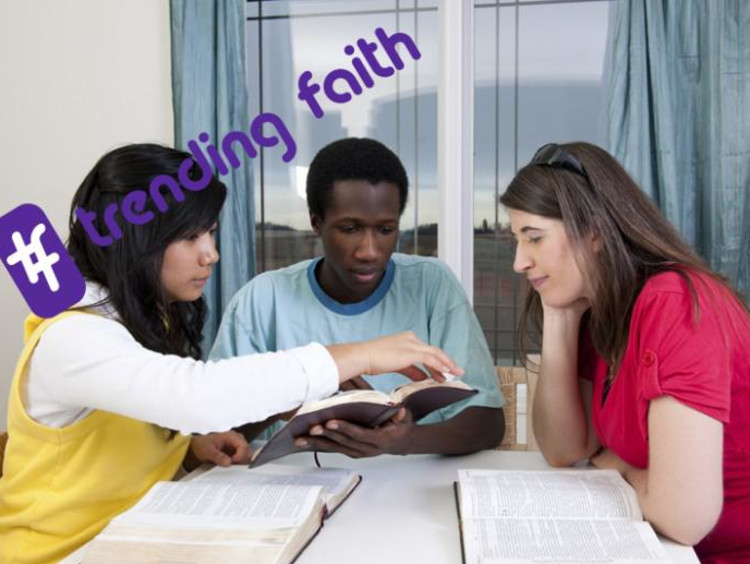 A group of people sitting around a table with the trending faith logo