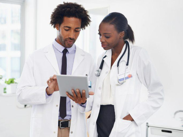 Two African-American doctors review results on tablet