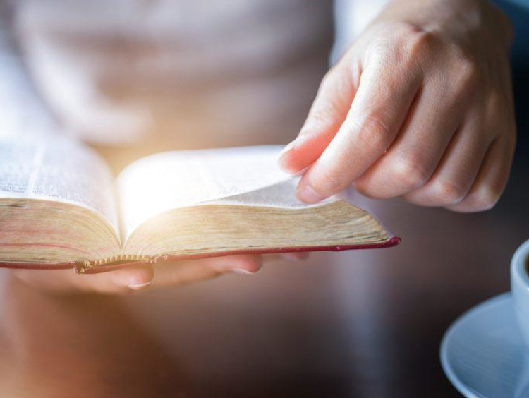A hand turning a page in a Bible