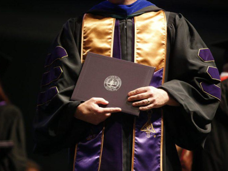 Doctoral student in graduation gown holds GCU diploma folder