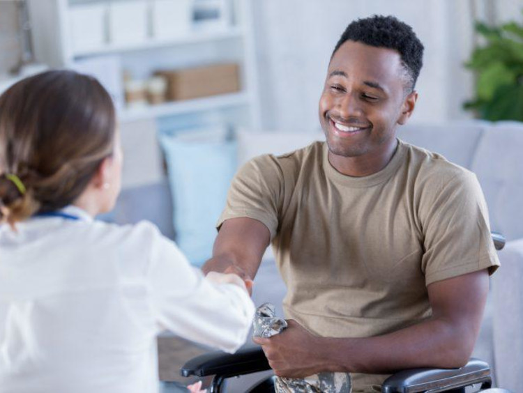 Female doctor shakes hand of African-American male patient who is smiling in wheel chair