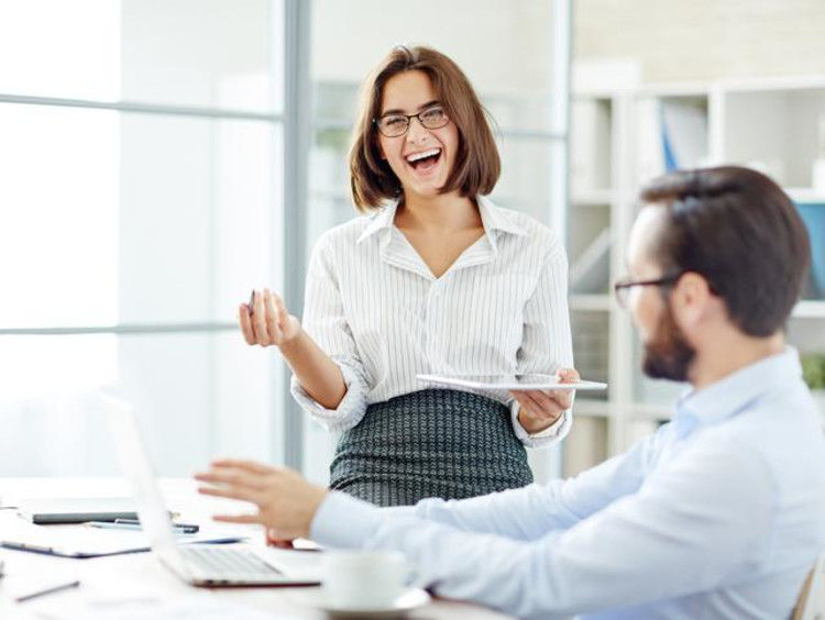 Woman laughs in an open office space while a man sits at a desk