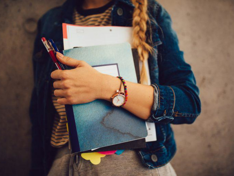 Teenage girl holding books, notebooks and pencils standing against wall