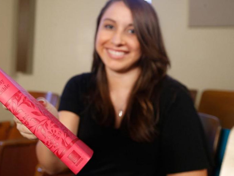 woman holding a bible close to camera