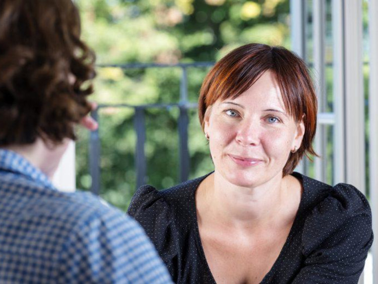 Woman with short red hair breaks a small smile facing a man with longer curly hair