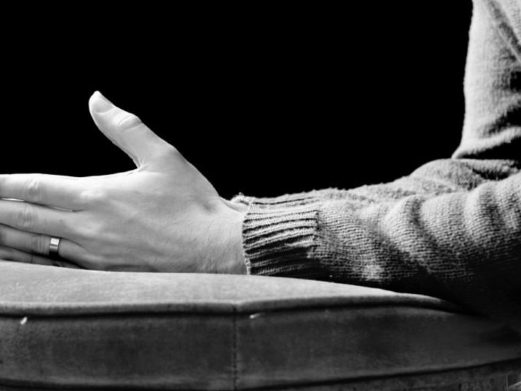 A black and white image of folded hands