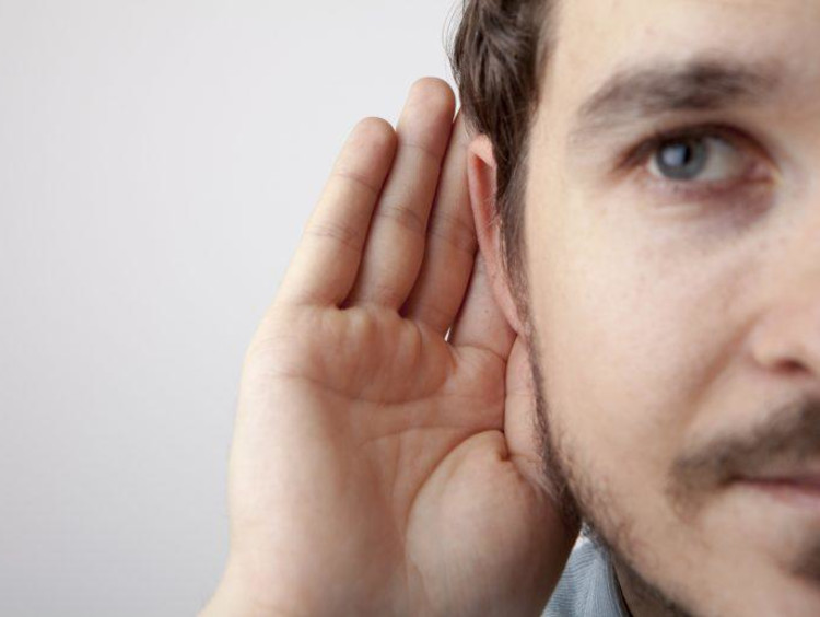 Man holding his hand to his ear to listen