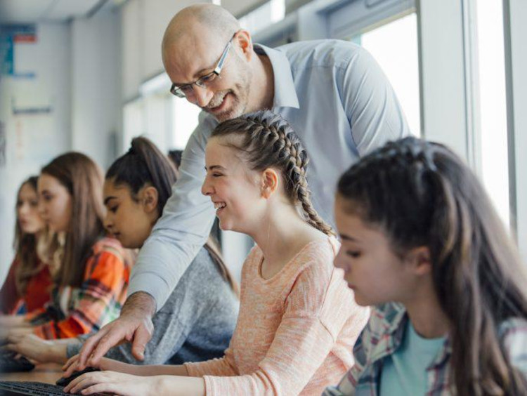 Adult man helping group of girls at school