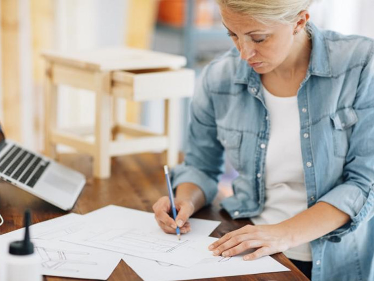Middle-aged woman works on a table sketch design